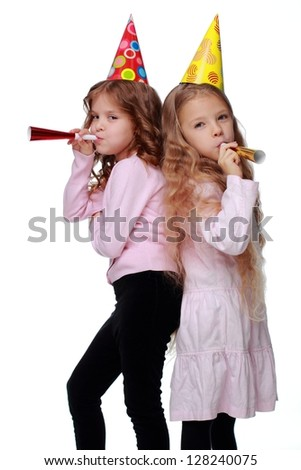 Studio image of two friends with toy horns isolated on white background on Holiday theme/Joyful girls