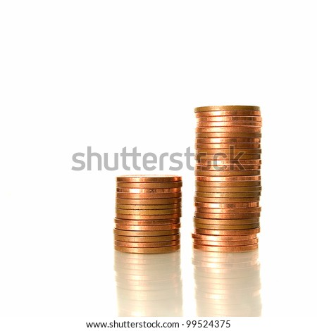 Studio image of two stacks of UK coins on a reflective surface against white background. Copy space. - stock photo