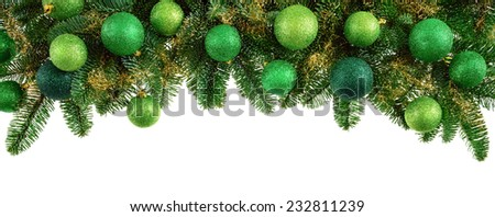 Studio isolated lush fir twigs with green baubles as a bow-shaped border on pure white background - stock photo