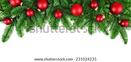 Studio isolated lush fir twigs with red baubles as a bow-shaped border on pure white background - stock photo