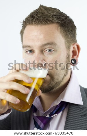 Studio Isolation of a single caucasian male. A close up shot of head and shoulders while the male has a rink from his pint of lager. The male is dressed in a suit but is untidy.