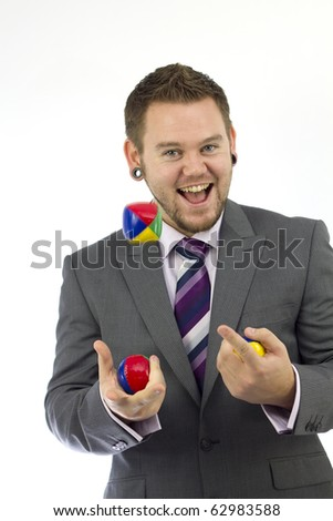 Studio Isolation of a single caucasian male. He is a Businessman, and he can juggle. Displaying the ability to juggle your business. He is smiling and ponting at the ball.
