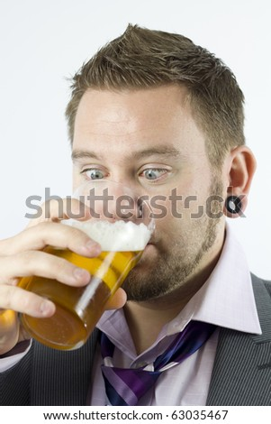 Studio Isolation of a single caucasian male. He is drinking a pint of lager whilst staring into his pint glass. - stock photo