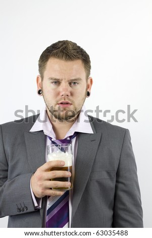 Studio Isolation of a single caucasian male. He is holding a pint of beer and has an empty expression whilst looking rather drunk.