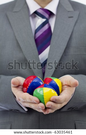 Studio Isolation of a single caucasian male. He is holding 3 Juggling balls in front of him. A conceptual image to display juggling in business. Selective focus on the juggling balls