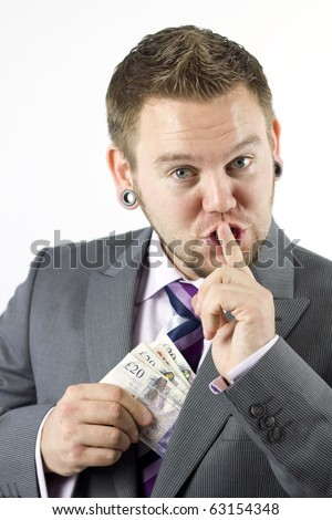 Studio Isolation of a single caucasian male. He is putting a handful of money into his jacket as if he were stealing it whilst holding his finger over his mouth telling you to keep quiet.