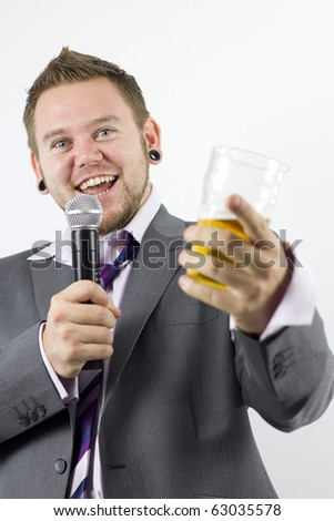 Studio Isolation of a single caucasian male. He is Smiling at the camera whilst singing down a microphone and holding a pint of lager. He is also pointing at the camera.