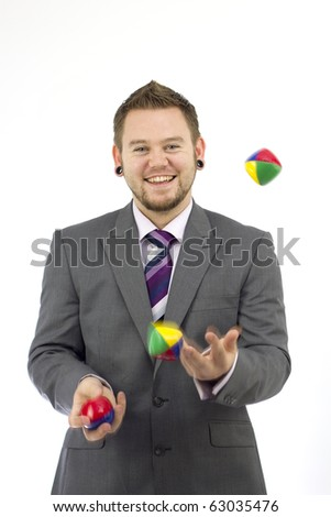 Studio Isolation of a single caucasian male. He is wearing a suit and is a smart businessman that can juggle well. Whilst he is juggling he is looking into the camera and giving us a smile.