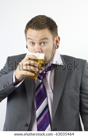 Studio Isolation of a single caucasian male. His eyes are wide open whilst he guzzles a pint of lager looking into the camera.
