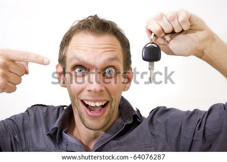 Studio Isolation of a single caucasian male. Male holds a car key while points at it smiling happily. Isolated against white. Copy Space provided.