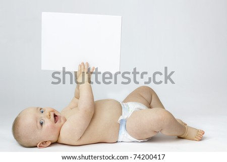 Studio Isolation of an Infant Child. The baby boy is Isolated on white with a Horizontal composition. He is laid on his back smiling into the camera whilst holding a white board in the air.