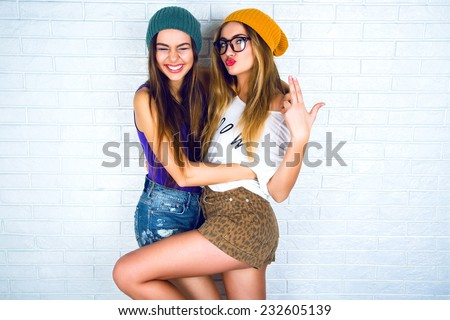 Studio lifestyle portrait of two best friends hipster girls wearing stylish bright outfits, hats, denim shorts and glasses, going crazy and having great time together. White urban wall background.  - stock photo