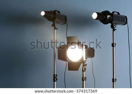 Studio light flashes on light blue wall background - stock photo