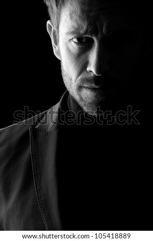 Studio low key portrait in black and white of a mid age man wearing a blazer. - stock photo