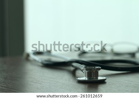 Studio macro of a stethoscope and glasses with shallow DOF evenly matched abstract on wood table background copy space - stock photo