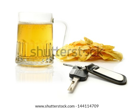 Studio macro of pint of beer, scattered potato chips (crisps) and car keys on a white surface. Concept image for drink driving. Copy space. - stock photo