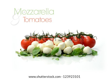 Studio macro of ripe tomatoes and mozzarella balls garnished with chopped basil. Copy space. - stock photo