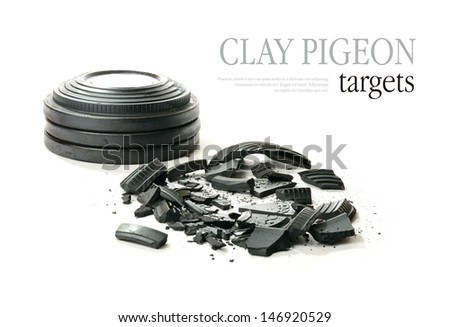 Studio macro of stacked clay pigeon targets and shattered clay with soft shadows against a white background. Copy space. - stock photo