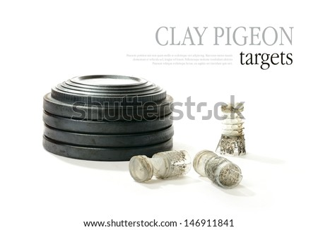 Studio macro of stacked clay pigeon targets and spent shotgun cartridges with soft shadows against a white background. Copy space. - stock photo