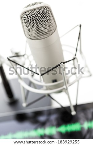 Studio microphone for recording podcasts and computer tablet on a white background.