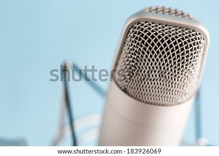Studio microphone for recording podcasts on a blue background. - stock photo