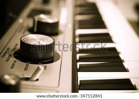 studio music synthesizer keyboard, shallow dept of field & focus on big knob + sepia filter - stock photo