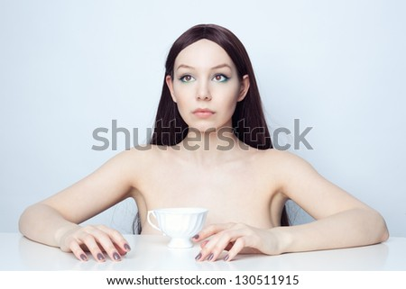 Studio photo brunette at the table. - stock photo