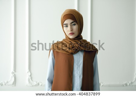 Studio photo of a beautiful young woman dressed oriental type in the Muslim style - stock photo