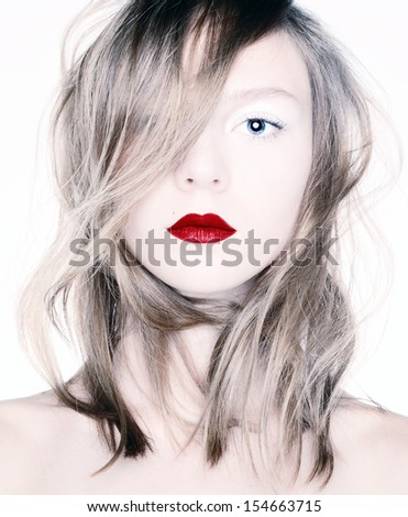 Studio photo of a young blonde with red lips.
