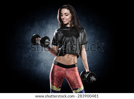 Studio photo of attractive female bodybuilder working out.