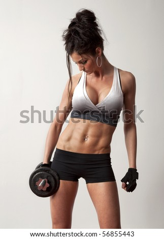 Studio photo of attractive female bodybuilder working out. - stock photo