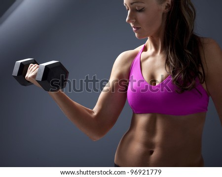 Studio photo of attractive young woman lifting dumbbell. - stock photo