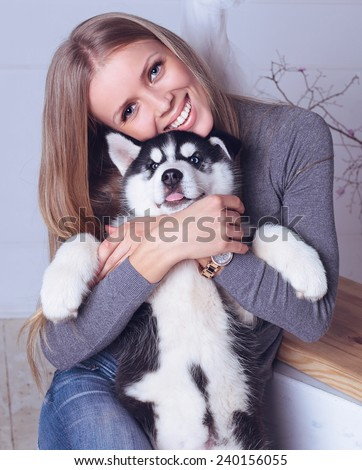 Studio photo of beautiful blond girl with long straight hair,big smile, white teeth wearing in gray sweater, jeans and holding a cute little puppy of Husky - stock photo
