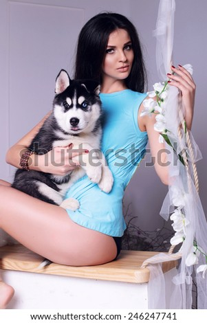 Studio photo of beautiful sexy brunette women with long straight hair wearing in blue top relaxing at home,sitting on a swing and holding a cute little dogs of Husky - stock photo