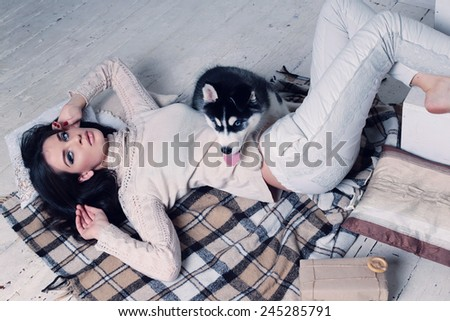 Studio photo of beautiful sexy brunette women with long straight hair wearing in cream sweater relaxing at home,sitting on the wood floor near staircase,and holding a cute little dogs of Husky - stock photo