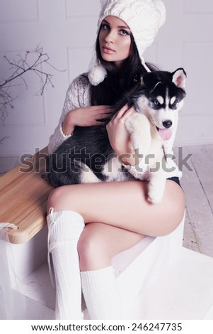Studio photo of beautiful sexy brunette women with long straight hair wearing in sweater, knit hat with bubonic relaxing at home,sitting on a swing and holding a cute little dogs of Husky - stock photo