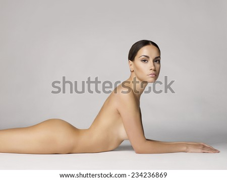 studio photo of elegant naked lady laying on white background - stock photo