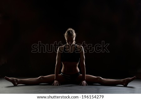 studio photo of fitness instructor stretching her middle splits - stock photo