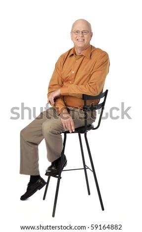 Studio photo of happy, mature man seated on black stool. White background. - stock photo