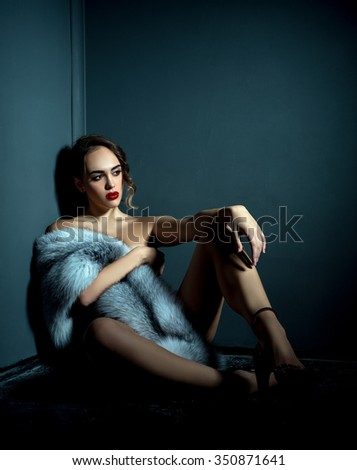 Studio photo of naked girl with expensive fur coat