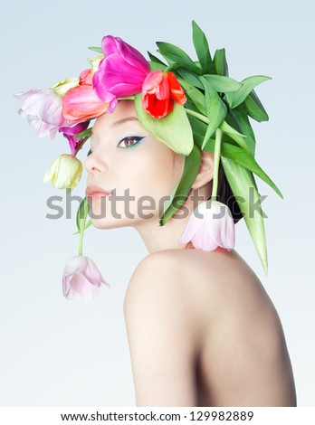 Studio photo of the girl with a wreath of tulips. - stock photo