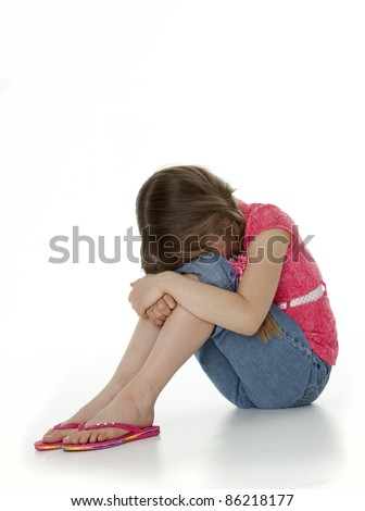 Studio photo of young girl seated on floor hugging knees, face obscured, on white background.