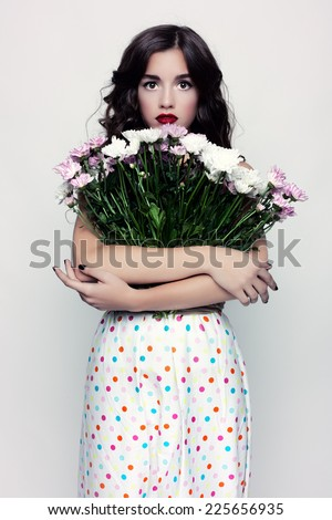 Studio photo rustic young woman with a bouquet of wildflowers. - stock photo