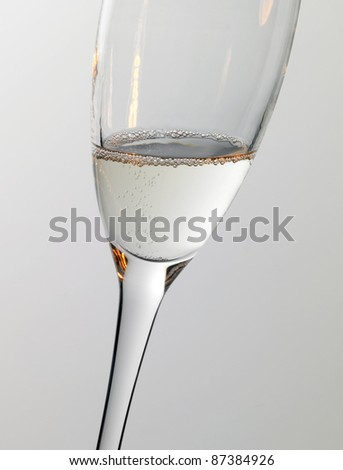 Studio photography of a champagne glass detail with warm light effects in grey back