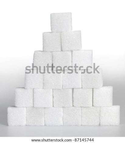 Studio photography of a pyramid made of lump sugar pieces in light gradient back - stock photo