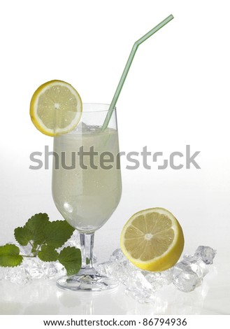 studio photography of a translucent soft drink with sliced lemon and drinking straw in light back with lemon fruits and ice cubes - stock photo
