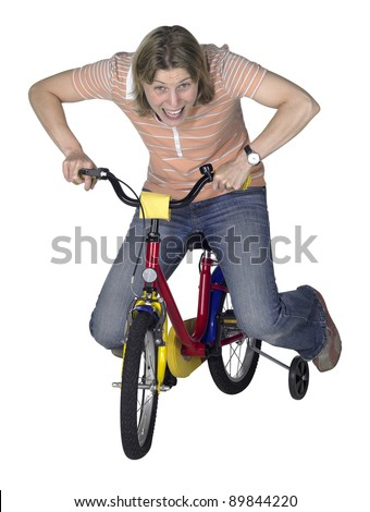 studio photography showing a crazy driving girl on a juvenile bicycle in white back