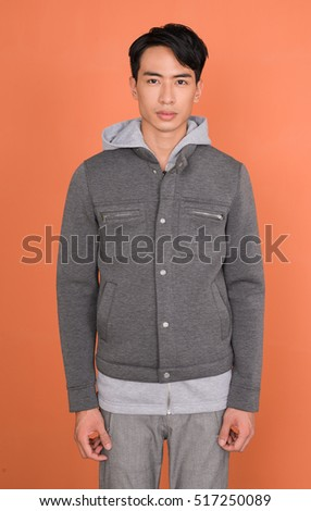 Studio picture of a young handsome man -orange background
