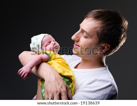 Studio picture of happy young father with his 14 days old newborn daughter over black background - stock photo