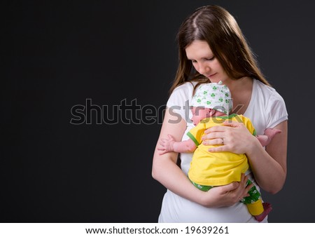 Studio picture of happy young mother with her 14 days old newborn daughter over dark background - stock photo